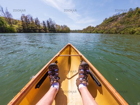 Man in small yellow pack canoe paddling down the Monongahela river in Morgantown