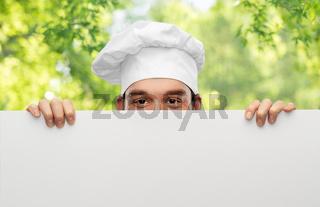 male chef hiding behind big white board