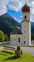 church in the alps mountains sun grass clouds