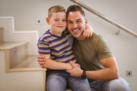 Portrait of caucasian father and son smiling sitting on the stairs at home