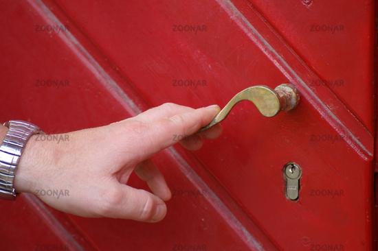 Hand öffnet Tor oder Tür