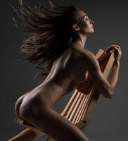 Slim naked brunette on wooden chair rearview