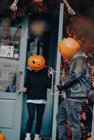 Couple with pumpkin heads posing on camu at the building