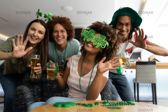 Portrait of diverse group of happy friends celebrating st patrick's day holding beers and waving