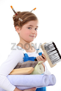little girl in overalls holding painting materials