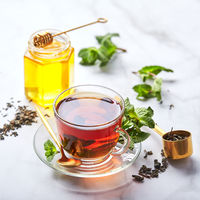 Black tea in glass transparent mug with mint leaves and honey. Calming and revitalizing tea, anti-stress and relaxation