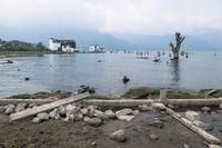 House at the coast of lake Atitlan with dead tree along misty mountains, San Pedro la Laguna, Guatemala