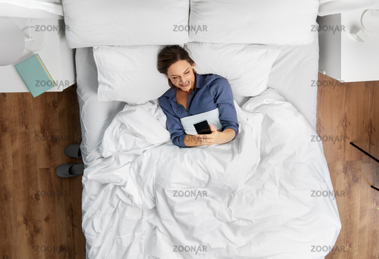 young woman with smartphone lying in bed
