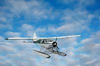 Kleines Wasserflugzeug ueber den Wolken