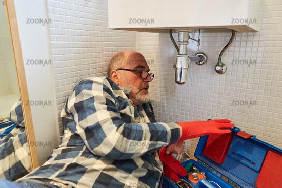 Klempner bei der Montage vom Waschbecken im Bad