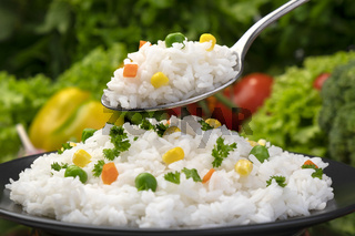 Cooked rice porridge, served with herbs and vegetables on black plate