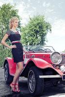 elegant girl poses near the car