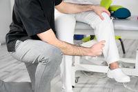 Neurological examination. The neurologist testing reflexes on a female patient using a hammer.