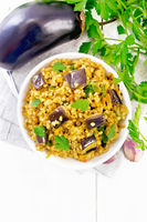 Bulgur with eggplant in bowl on light board top