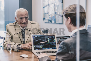Financial advisor consulting senior client with his investment strategy.