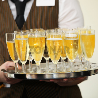 Waiter carrying a tray of champagne