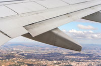 View from passenger window of commercial airplane, blurred urban landscape visible under aircraft wing