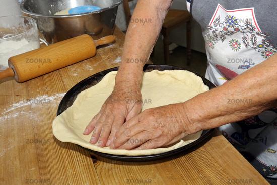 Kuchenblech mit Teig auslegen