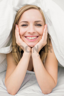 Closeup portrait of beautiful woman under sheet in bed