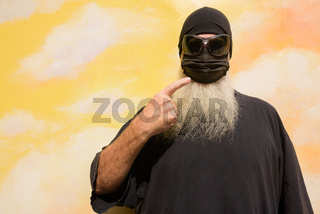 Summer portrait of mature man with long gray beard against cloudy background wall wearing face mask to protect from Covid-19 while pointing finger to surgical mask