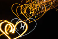Neon hearts on black background at night