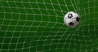Football ball scoring in goal net over green pitch