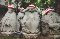 Detail of Buddha statues with knitted hat offerings at the temple Diasho-in in Miyajima, Hiroshima, Japan
