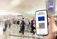 EU Digital COVID Certificate with the QR code on the screen of a mobile held by a hand with blurred airport in the background