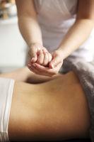 Crop masseuse using massage oil during skincare procedure