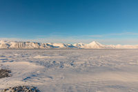 Arctic winter landscape with frozen fjord and snow covered mountains on Svalbard, Norway