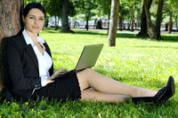 Businesswoman relaxing with laptop in park