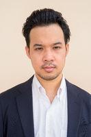 Portrait of Asian businessman wearing suit against plain background