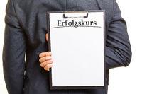 Business Mann mit Klembrett und Erfolgskurs Slogan