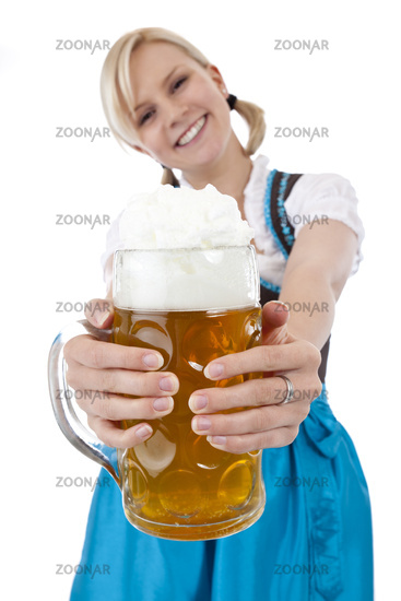 Hübsche blonde Frau im Wiesn-Dirndl prostet mit Masskrug zu