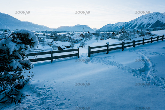 Alpine winter landscape during dusk with view over small Austrian traditional village in Wildermieming, Tirol, Austria