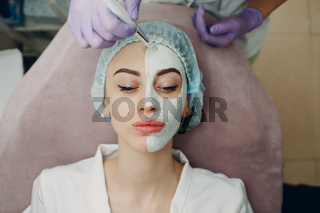 Young woman applying mask of clay on face in beauty spa
