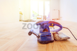 Renovating at home: sander tool for refreshing and grinding the wooden parquet floor