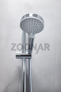 Shower head on a gray microcement wall of a modern bathroom