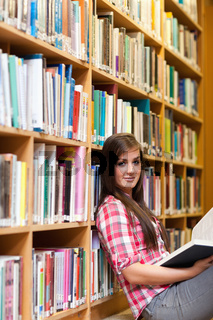 Portrait of a young female student holding a book
