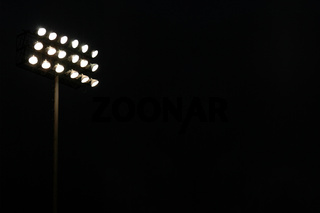 Stadium flood lights on a sports field at night with copy space