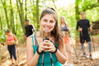 Lächelnde Frau mit Freunden beim Nordic Walking