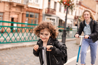 The girl rides a scooter for the first time together with her mom
