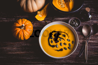 Homemade pumpkin soup with pumpkin oil and seeds on wooden background