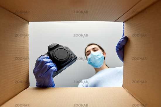 woman in mask packing camera into parcel box