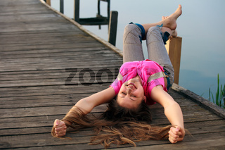 Relaxing young woman lying on the bridge