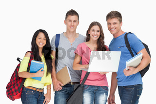 A smiling group of students holding a laptop while looking at the camera