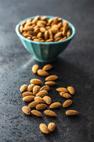 Almond nuts in bowl on black table.