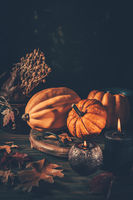Still life for Thanksgiving with pumpkins and autumn leaves  on wooden background
