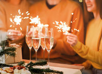 Glasses of champagne on table with blurred background of festive lights and sparkles