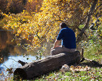 Man sitting with his back on wooden log by river